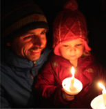 father, mother and child celebrating Winter Solstice with candle burning.